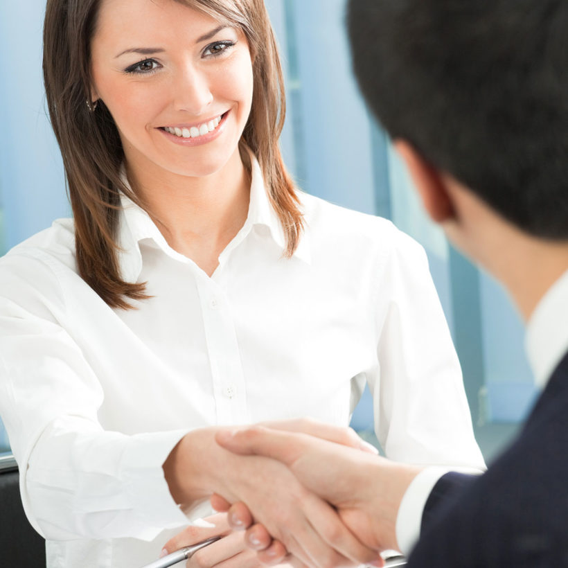 Happy woman shaking hands in agreement of the business insurance policy in Farmingdale